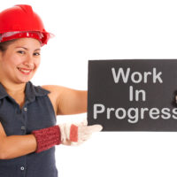 Work In Progress Sign Held By Construction Worker