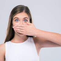 Female teenager covering her mouth