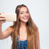 Cheerful woman making selfie photo on smartphone