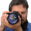 Earth in camera lens, man shooting photo