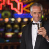 Man in tuxedo drinking champagne in casino