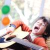 Kid singing and playing guitar at home
