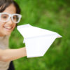 Kid flying a paper airplane